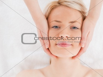 Smiling blond-haired woman getting a massage on her face