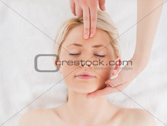 Attractive blond-haired woman getting a massage on her face