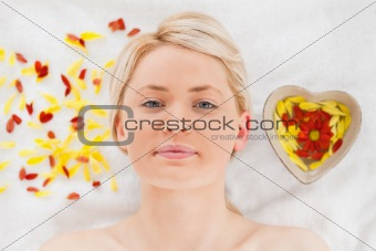 Attractive blonde woman lying down near flower petals