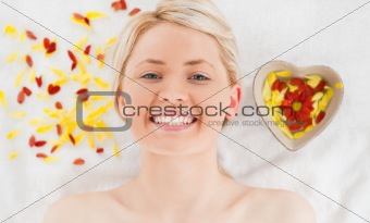 Cute woman lying down near flower petals