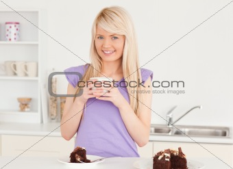 Smiling blonde woman eating cake and drinking coffee