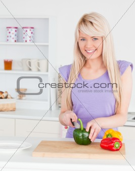 Attractive blonde female cutting vegetables in modern kitchen in