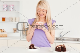Attractive blonde woman eating cake and drinking coffee