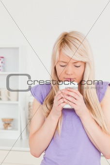 Attractive blonde woman drinking hot drink