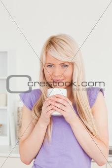Attractive blonde female drinking hot drink