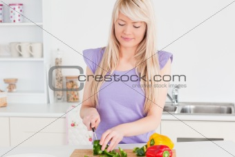 Smiling blonde woman cutting vegetables in modern kitchen interior