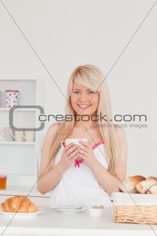 Beautiful blonde woman having her breakfast in the kitchen