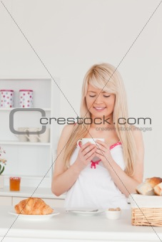 Beautiful blonde female having her breakfast in the kitchen