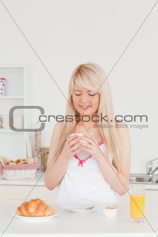 Gorgeous blonde female having her breakfast in the kitchen