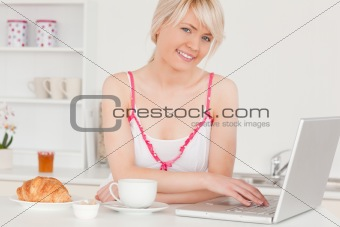 Beautiful woman having her breakfast while relaxing with a lapto