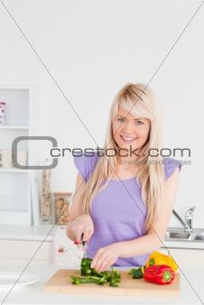 Gorgeous blonde female cutting vegetables in modern kitchen inte