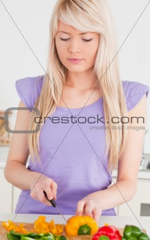 Smiling blonde woman cutting peppers in modern kitchen interior