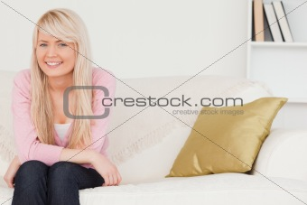 Attractive blonde woman posing while sitting on a sofa