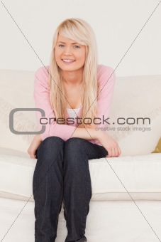 Attractive blonde female posing while sitting on a sofa