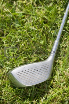 Golf club driver laying in grass, concept photography