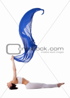 woman lay in yoga pose with blue flying fabric