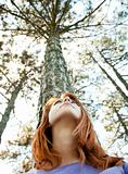 Beautiful redhead girl at the park in summer time looking up.