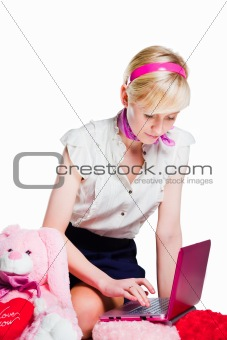 beautiful blond girl working with pink laptop on isolated white