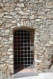 door made of bars in the old stone wall