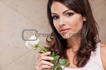 Attractive young female holding a white rose