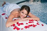 Smiling young woman at spa with rose petals around