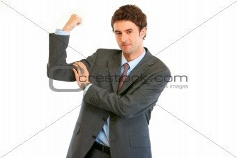 Confident young businessman showing his  muscles