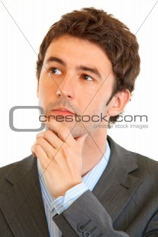 Portrait of serious modern businessman looking in corner at copy space