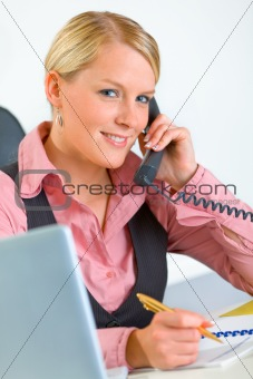 Smiling business woman sitting at office desk and talking on phone