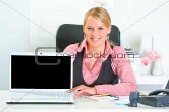 Smiling business woman sitting at office desk and showing laptop with blank screen