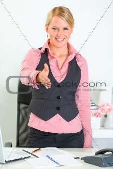 Smiling business woman standing near office desk and stretches out hand for handshake