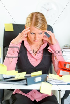 Tired business woman sitting at workplace overwhelmed with sticky reminder notes