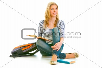 Smiling young girl sitting on floor with schoolbag and books and looking in corner at copy-space