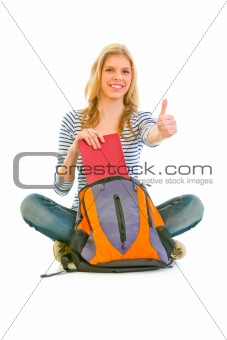 Sitting on floor smiling girl geting book from schoolbag and showing thumbs up gesture
