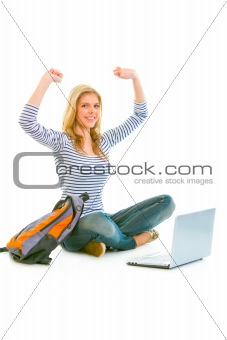Sitting on floor with schoolbag and laptop pleased teengirl rejoicing her success