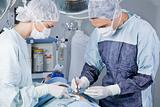 Medical professionals carrying on surgery on patient
