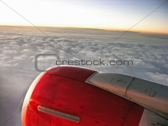 Airplane engine in sunset sky