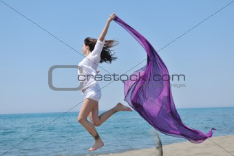 beautiful young woman on beach with scarf