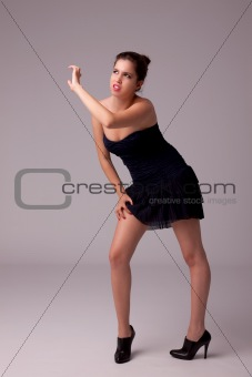 beautiful woman with elegant dress looking up protection with the arm from the light, sitting on a bench, studio shot.