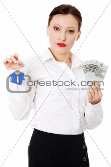 Beautiful businesswoman holding euros bills and hose keys