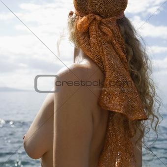 Topless woman at coast.