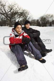 Boys sitting in snow.