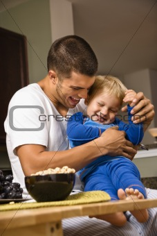 Dad tickling son.