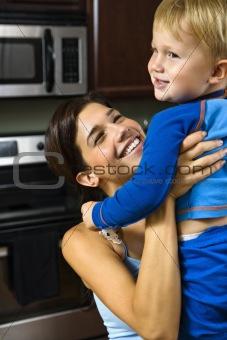 Mom lifting happy child.