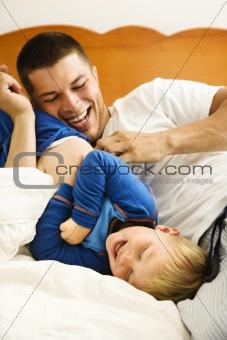 Dad tickling child.