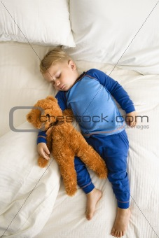 Toddler sleeping with bear.