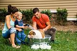 Family giving dog a bath.