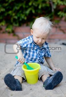 toddler playing in sandbox