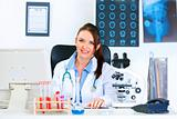 Smiling medical doctor woman sitting at table in her office