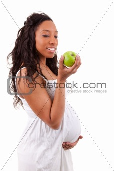 Pregnant african american woman eating an apple