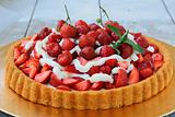 Plate with homemade strawberry tart with whipped cream